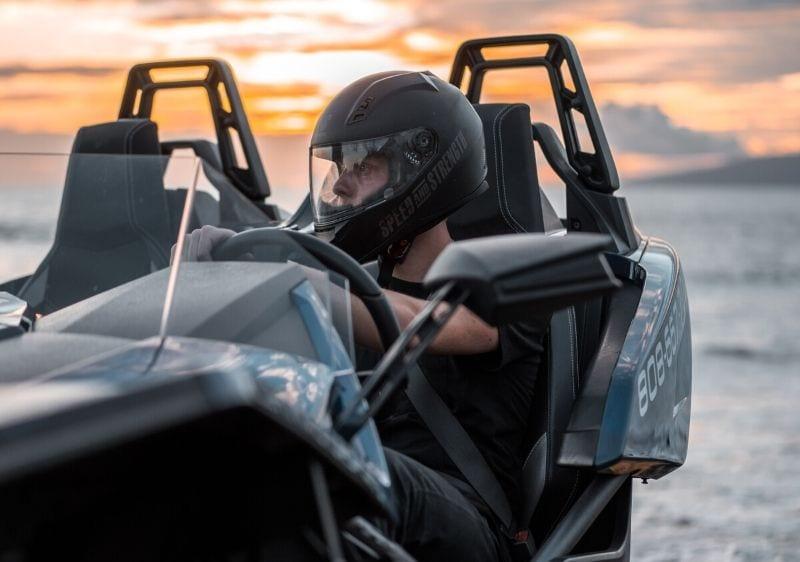 guest in a parked Polaris Slingshot by the coast of Hawaii