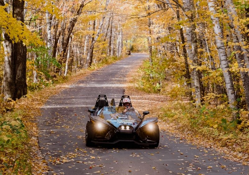 guest-driving-a-Polaris-Slingshot-through-a-tree-covered-road