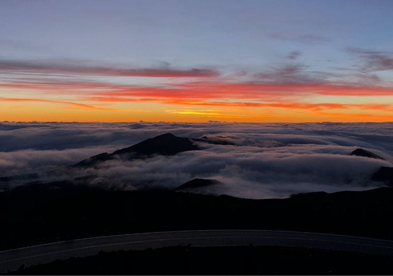 aerial view of a road along an overlook of clouds at sunrise from the Volcano Summit run
