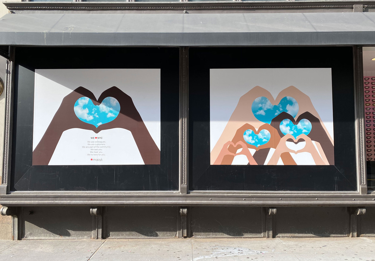 Department store windows featuring illustrated hands of different skin tones forming heart shapes around blue sky with clouds
