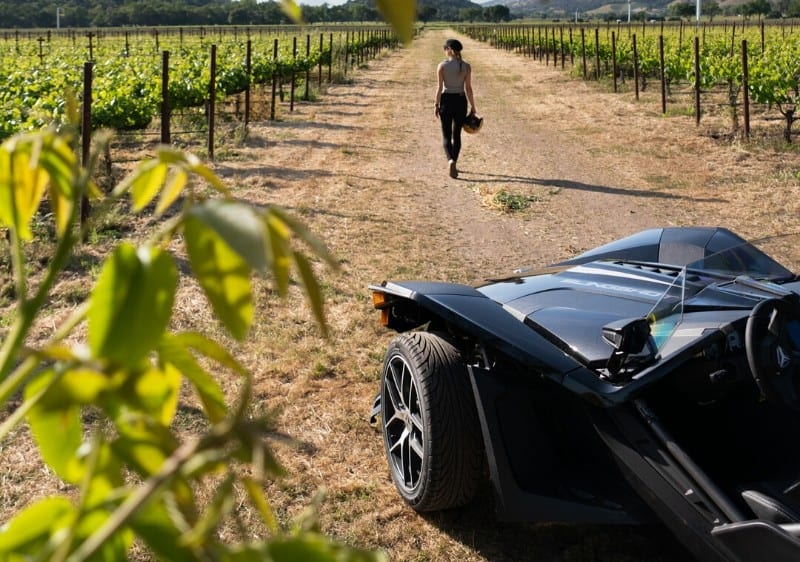 guest walking away from a parked Polaris Slingshot overlooking the views of the winery