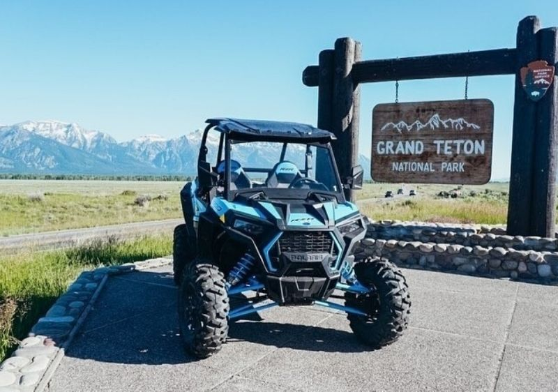 off-road vehicle next to Grand Teton National Park sign