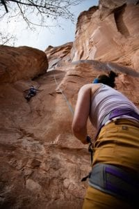 Rock climbers top roping outdoors with a belayer