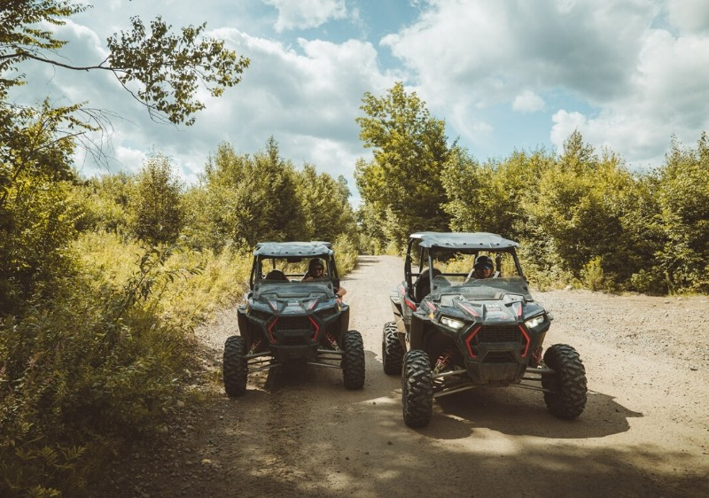 guests-driving-Polaris-RZRs-off-road-down-a-dirt-path