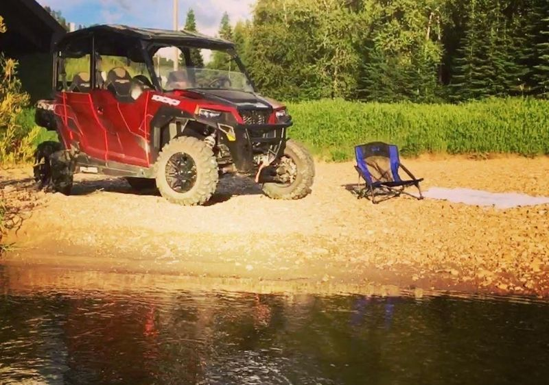 Polaris-General-parked-along-water-with-a-lawn-chair