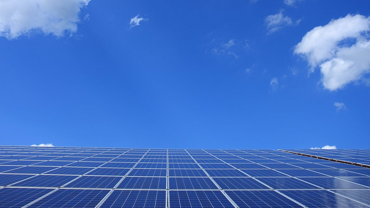 This photo is of solar panels on a roof with a blue sky in the background.