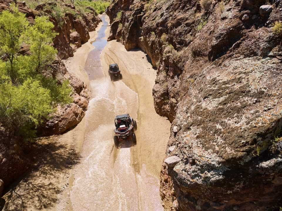 off-road vehciles driving through stream in slot canyon