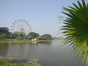 Inya Lake surrounded by greenery and a Ferris wheel in the distance