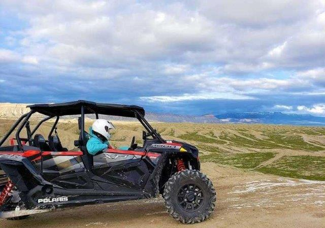 guests in an off road vehicle overlooking scenery