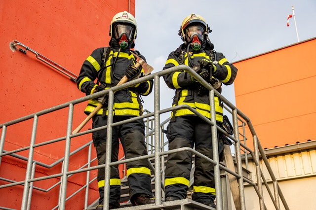 two-firemen-standing-on-stairs-3788978.jpg