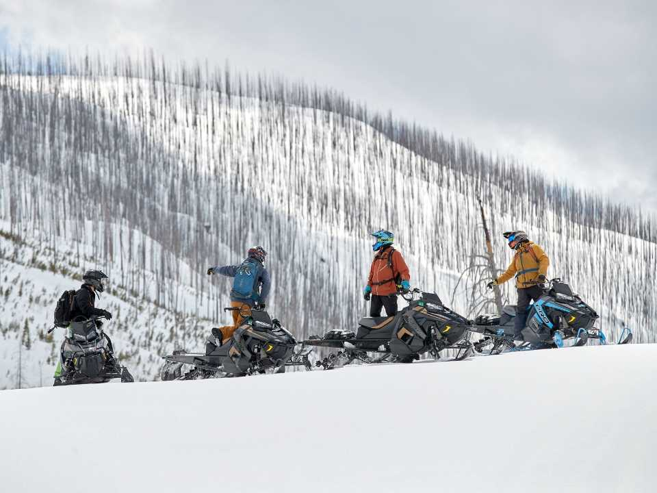 group of snowmobilers pointing at view