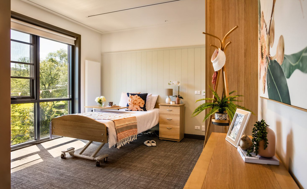This is a photo of a resident's room at BSL's aged care residence in Clifton Hill. The decor is yellow and white, and the room is bright and inviting.