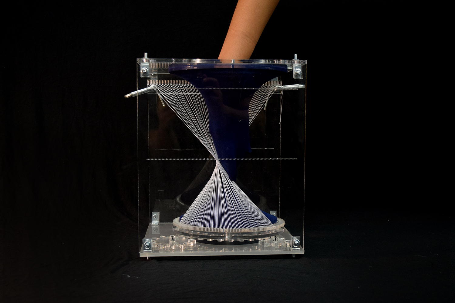hand fully inside textile form through a hole in one face of the vertical acrylic box