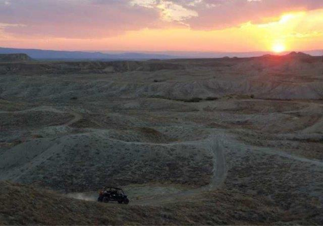 off-road vehicle driving along rocky sand mounds
