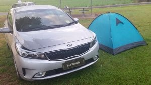 Silver Kia Rental Car with K Mart tent