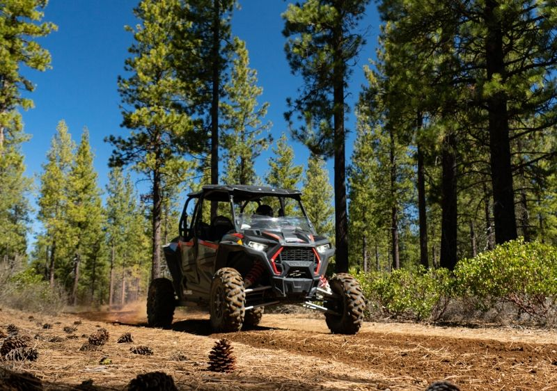 Polaris-RZR-parked-on-a-trail-surrounded-by-trees