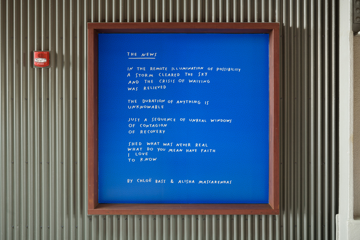 """Installation of poem titled """"The News,"""" printed in white on bright blue background, framed on a corrugated wall"""