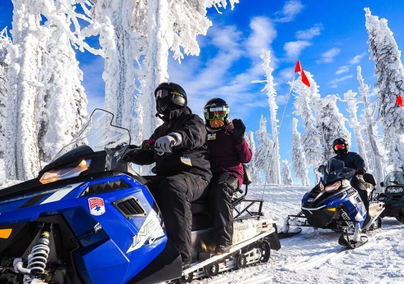 snowmobiling tour passenger waves snowy trees and blue skies
