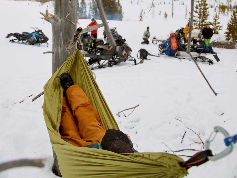 guest hammocking in full snow gear in mountains