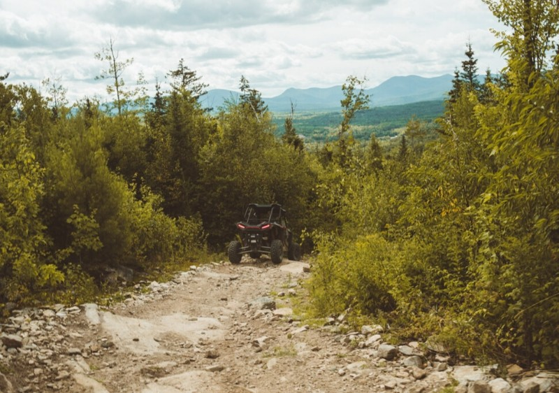 guests-driving-Polaris-RZR-down-a-rocky-trail-through-forested-area-overlooking-Appalachian-mountains
