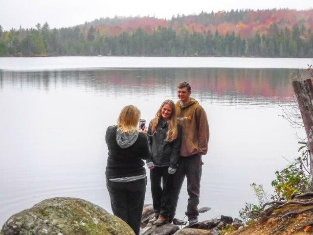 friends getting photo taken by a lake