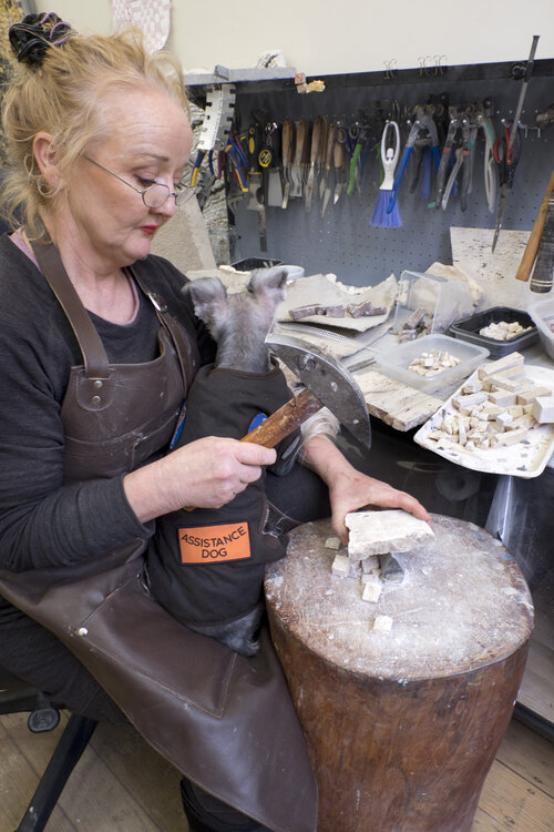 An artists sits at her workbench with her assistant dog, holding a hammer and chipping at stone