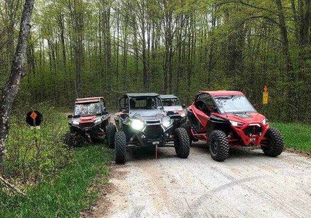 guests in Polaris RZRs parked on-a dirt trail