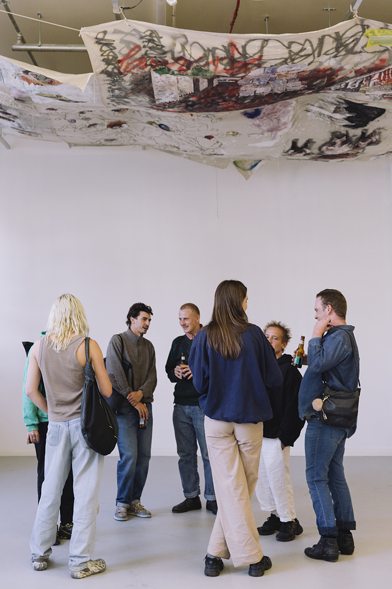 A crowd of exhibition goers gathers in Bus Projects gallery for the opening of an exhibition by Gian Manik