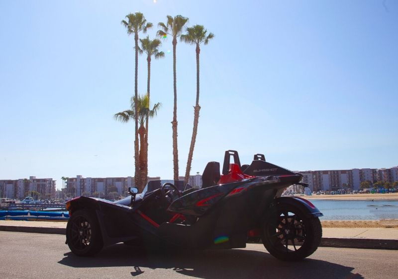 Polaris-Slingshot-driving-along-beach-resorts