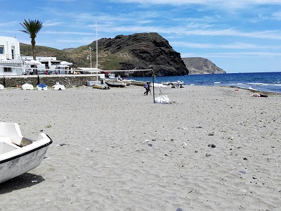 Upturned boats on the beach at Las Negras, volcanic rock down the coast, Cabo de Gata, Spain