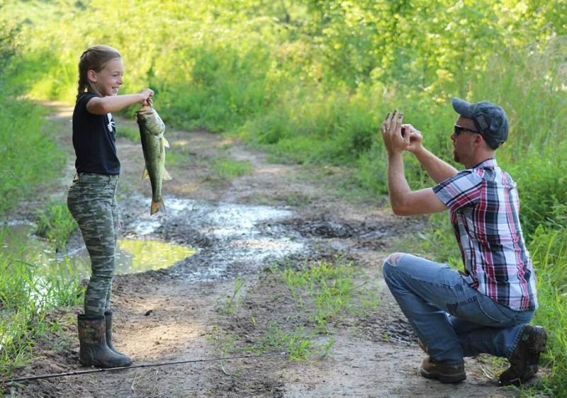 father-taking-a-photo-of-his-daughter-holding-a-fish
