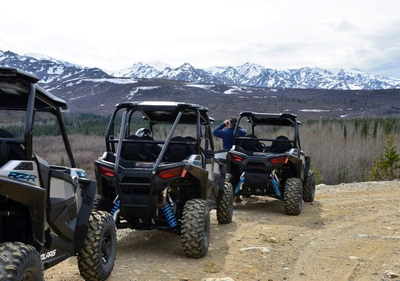 off-road vehicles parked near a the scenic mountain range