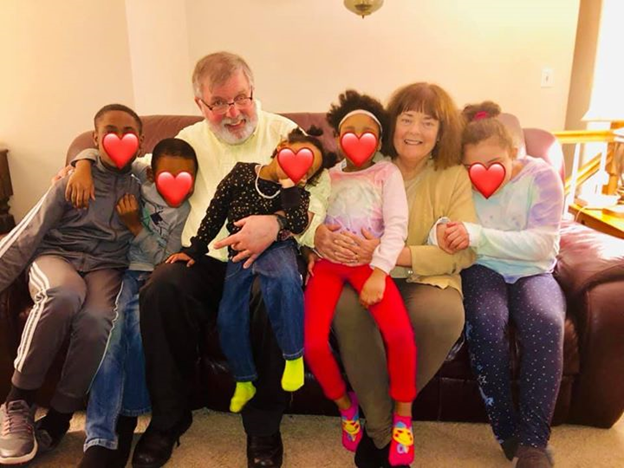 Five children nestled on a couch with foster parents Michael and Nancy Borghese, with hearts on the children's faces for privacy