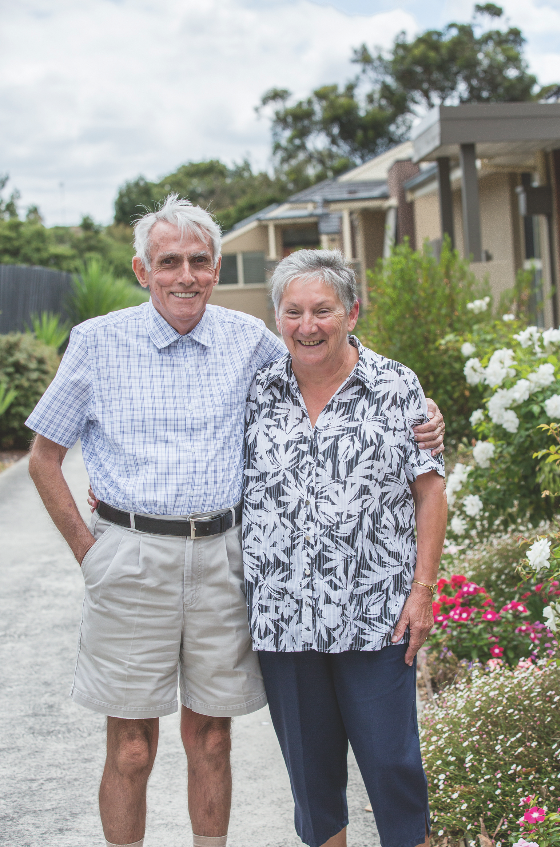 This is a photograph of an older couple standing outside the Banksia Centre. There are gardens in the background. The couple is smiling.