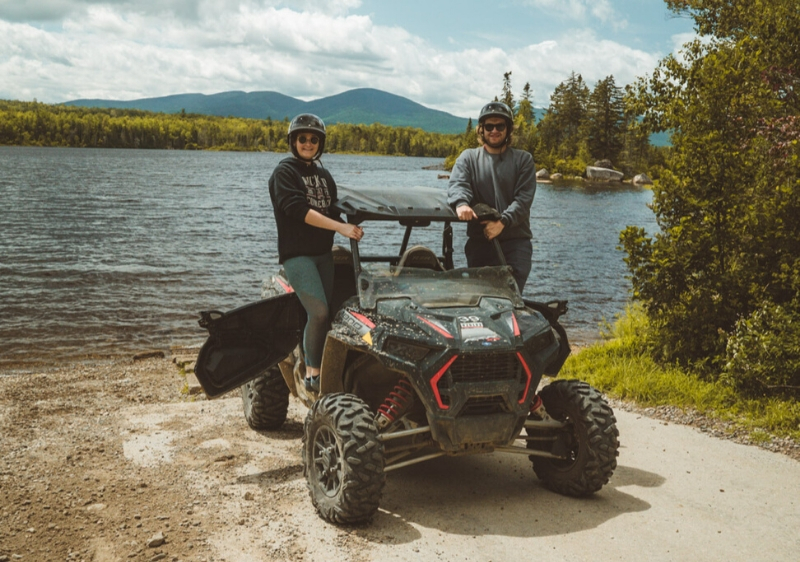 guests-posing-next-to-their-Polaris-RZR-in-front-of-a-scenic-lakeview-of-the-Appalachian-mountains