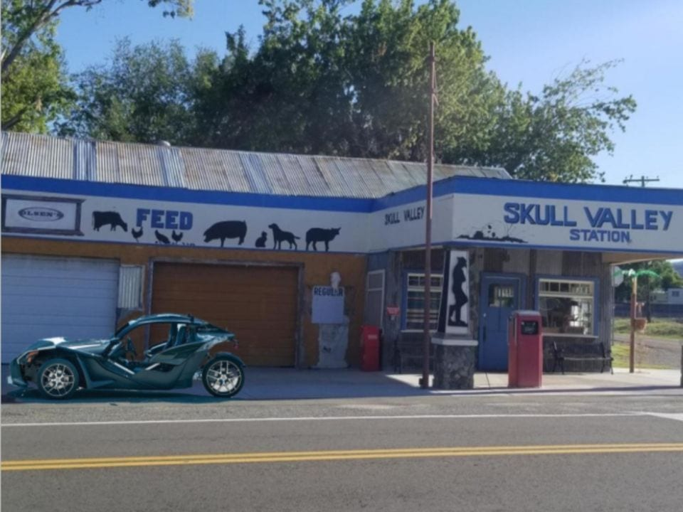 three wheeled vehicle parked at old fashioned gas station
