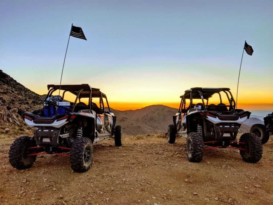 off-road vehicles parked in the desert at sunset