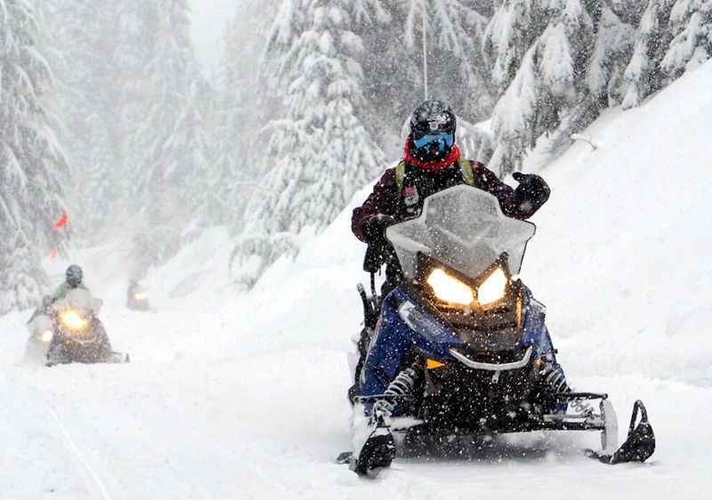 snowmobile tour guide leading in heavy snowstorm