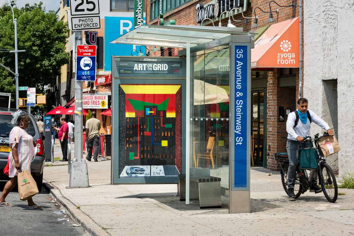 A Queens streetscape with a piece of public art by artist Jamaal Peterman installed in a bus shelter