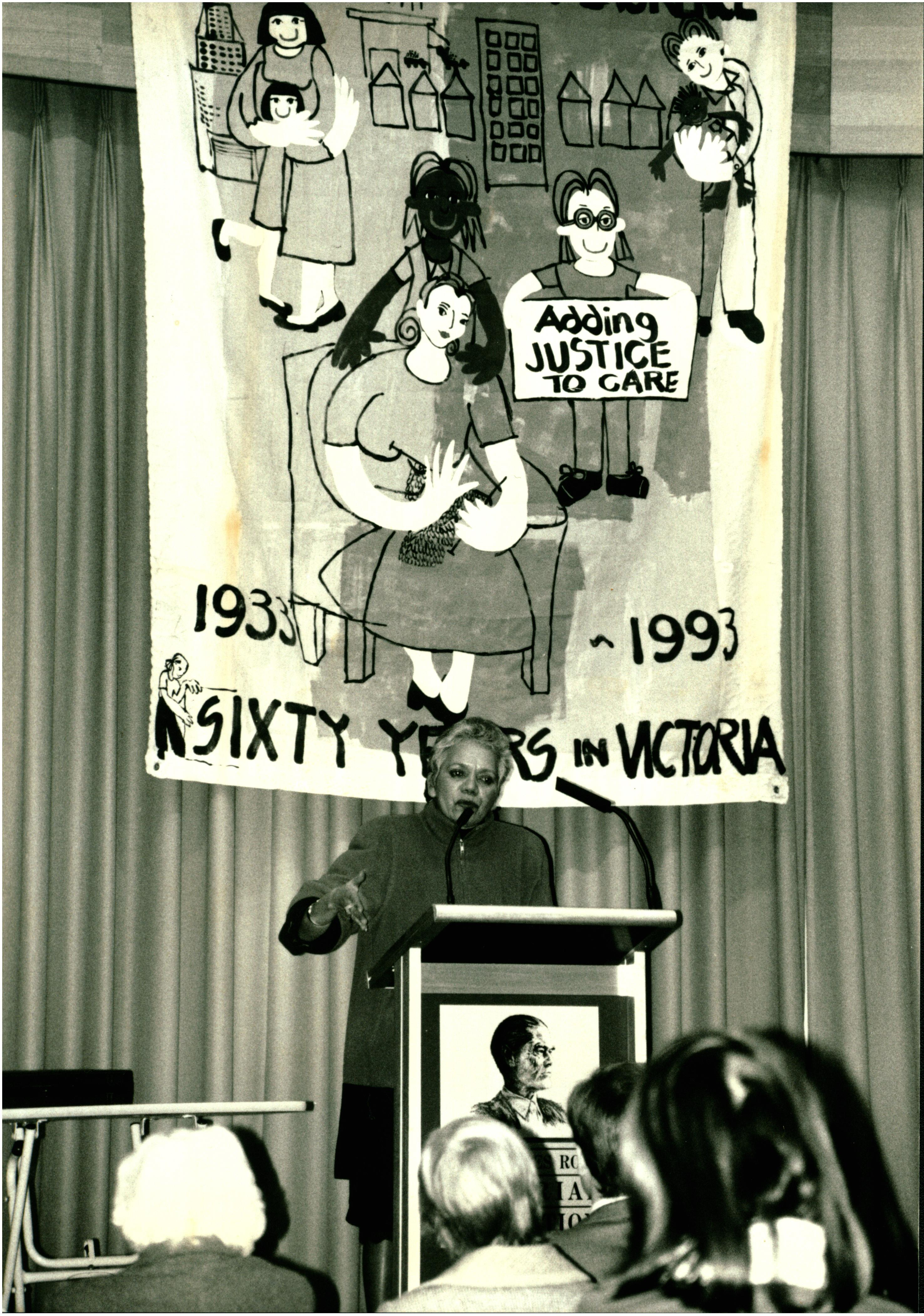 This is a black and white photo of Lillian Holt addressing the audience at the 1993 Sambell Oration. She is standing in front of a banner that says 'Adding justice to care' and '60 years in Victoria'