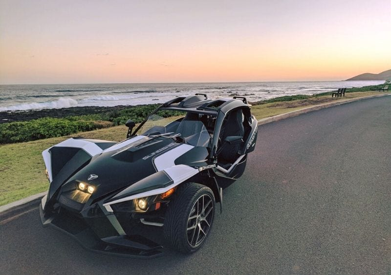 black Polaris Slingshot parked along a shoreline