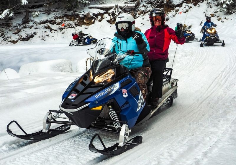 Snowmobiling-tour-group-driving-up-Priest-River-Valley-trail-waving