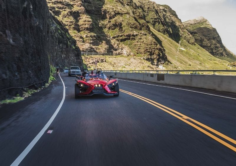 guests driving a Polaris Slingshot down a scenic highway