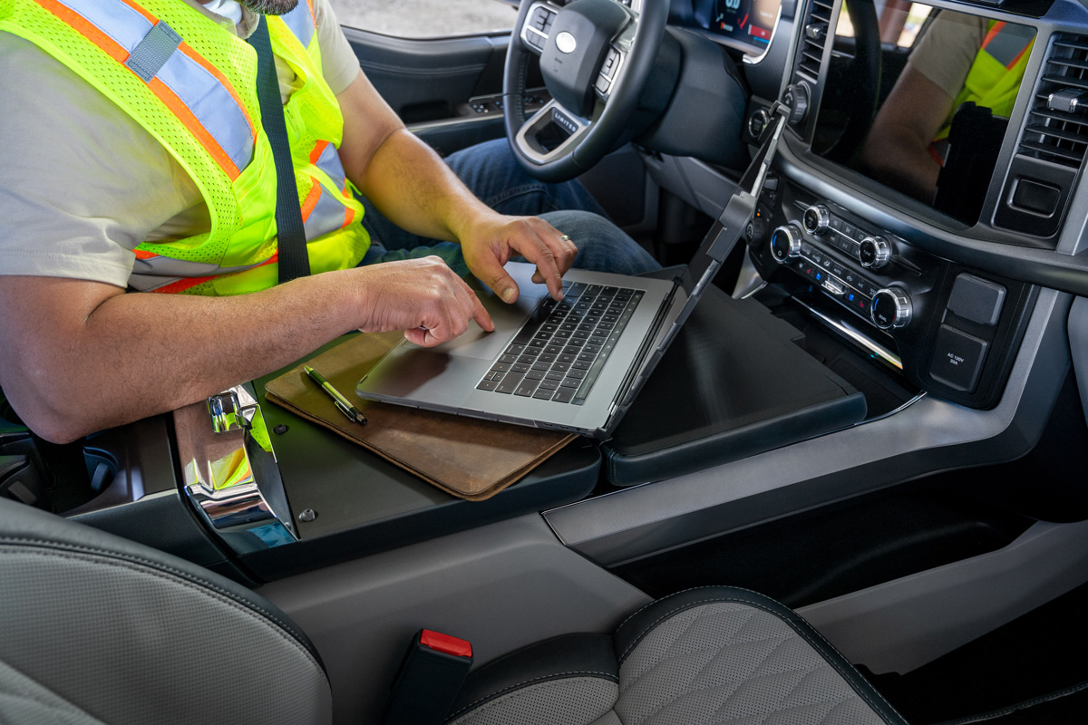 Auto console with hidden transmission shifter transformed into work surface for person in driver's seat typing on laptop