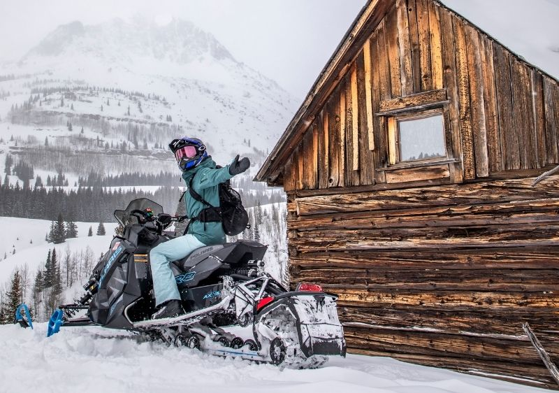 guest waving on snowmobile near wooden outhouse