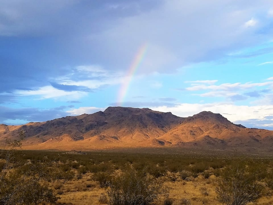 rainbow over desert mountain landscape