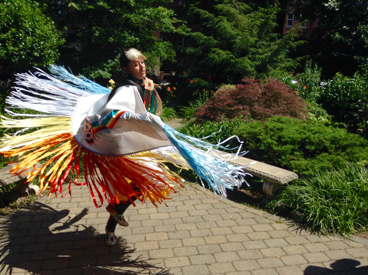 Dancer twirling in cape with long multicolored fringe, on sun-drenched brick path surrounded by lush greenery