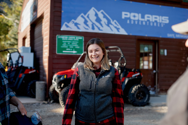 Guest-smiling-with-Polaris-Adventures-banner-behind-her