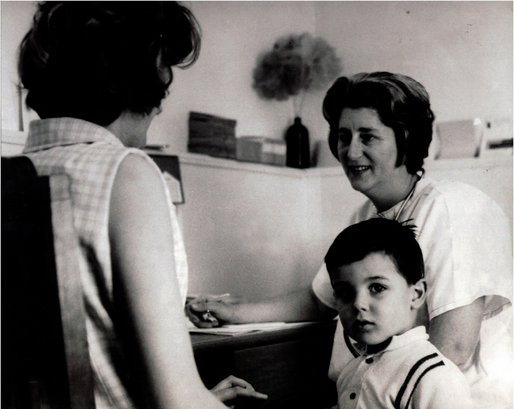 This is a black and white photograph of a mother and her young son talking to staff at the Family Planning Clinic