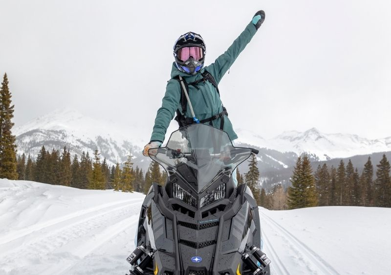 guest waving on snowmobile